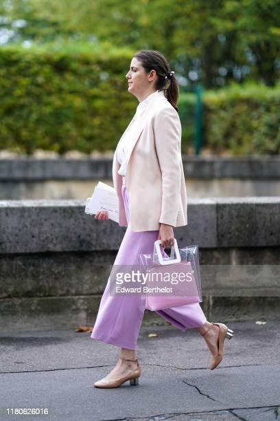 A guest wears a white plumetis shirt a beige jacket light mauve widelegs crop pants a transparent vinyl bag with a light pink clutch inside nudecolor...