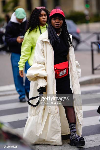 A guest wears a white puffer coat a red fanny pack belt bag outside Miu Miu during Paris Fashion Week Womenswear Spring/Summer 2019 on October 2 2018...