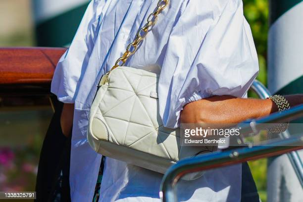 Guest wears a white puffy sleeves oversized shirt, a beige shiny quilted leather Marc Jacobs shoulder bag, a gold bracelet, during the 78th Venice...