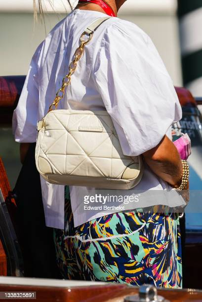 Guest wears a white puffy sleeves oversized shirt, multicolored print pattern large pants, a beige shiny quilted leather Marc Jacobs shoulder bag, a...