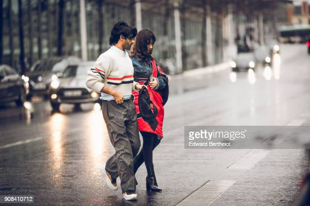 A guest wears a white pull over with red and blue stripes striped pants white sneakers a guest wears a blue denim jacket a red puffer coat black...