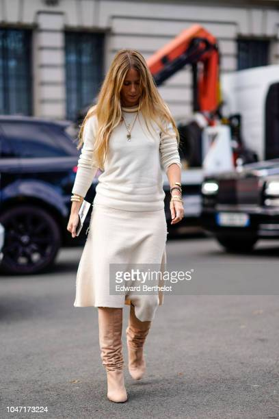 A guest wears a white pullover a golden necklace pink boots outside Akris during Paris Fashion Week Womenswear Spring/Summer 2019 on September 30...