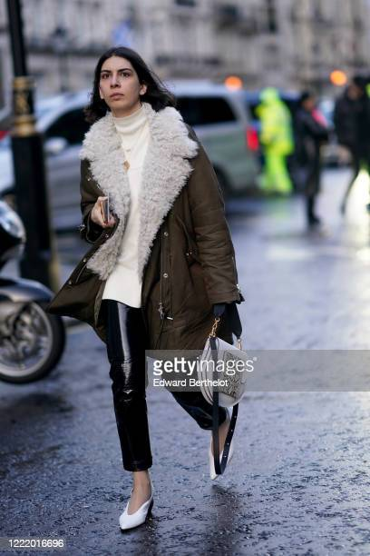 A guest wears a white pullover a khaki coat with white wool inner lining black shiny pants white pointy shoes a snake print bag during London Fashion...