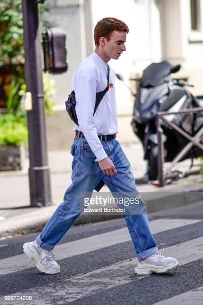 A guest wears a white pullover a shoulder strap bag blue jeans white sneakers shoes outside Wooyoungmi during Paris Fashion Week Menswear...