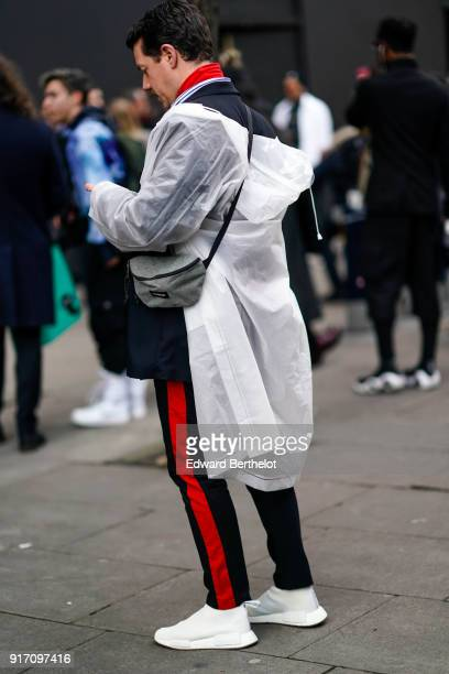 A guest wears a white rain coat sportswear pants white sneakers during London Fashion Week Men's January 2018 at on January 6 2018 in London England