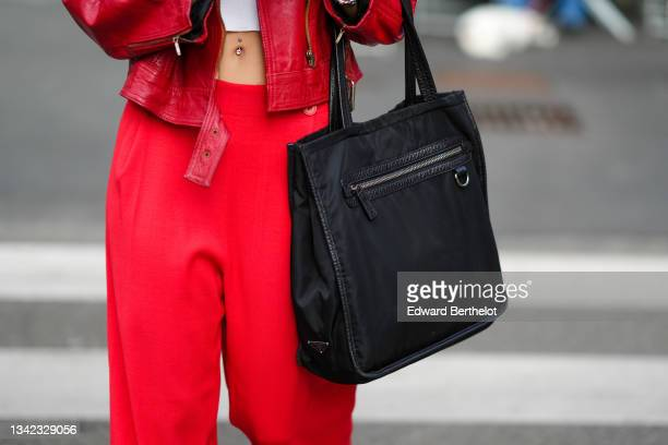 Guest wears a white ribbed cropped t-shirt, a red shiny leather oversized biker jacket, red high waist pants, a black large nylon gab from Prada,...