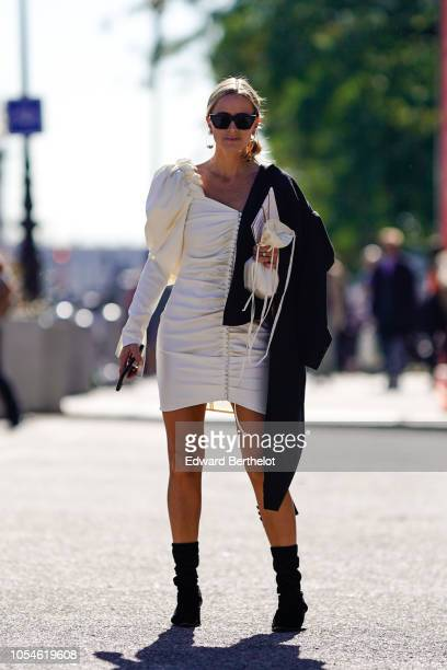 A guest wears a white ruffled dress with a black jacket outside Paco Rabanne during Paris Fashion Week Womenswear Spring/Summer 2019 on September 27...