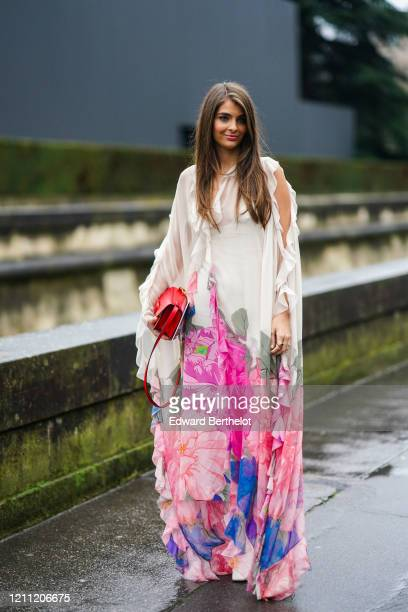 Guest wears a white ruffled dress with pink and blue floral prints, white boots, a red bag, outside Valentino, during Paris Fashion Week - Womenswear...