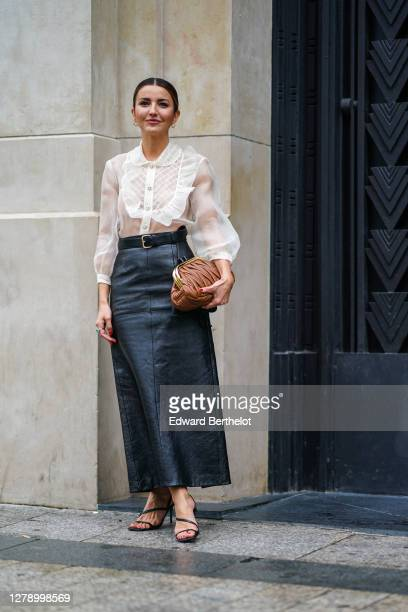 Guest wears a white ruffled mesh shirt, a belt, a black leather skirt, a brown leather Miu Miu bag, shoes, earrings, outside Miu Miu, during Paris...