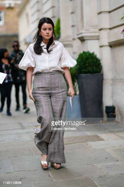 A guest wears a white ruffled shirt gray checkered flare pants during London Fashion Week September 2019 on September 16 2019 in London England