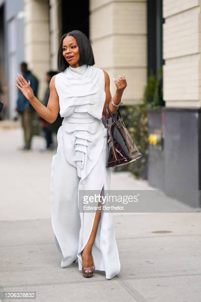 A guest wears a white ruffled sleeveless dress a shiny bag during New York Fashion Week Fall Winter 2020 on February 12 2020 in New York City