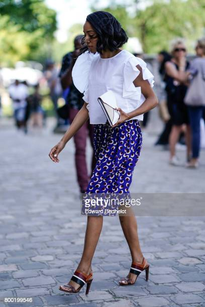 A guest wears a white ruffled top a blue skirt and heels outside the Cerruti show during Paris Fashion Week Menswear Spring/Summer 2018 on June 23...