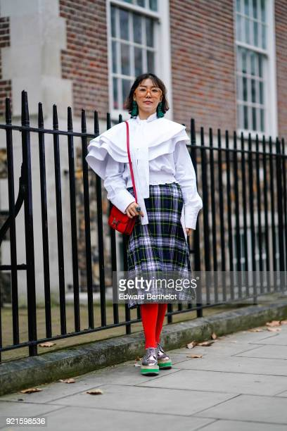 A guest wears a white ruffled top a red bag a checked skirt red tights sneakers shoes during London Fashion Week February 2018 on February 18 2018 in...