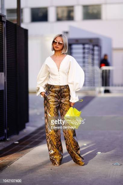 A guest wears a white ruffled top flare pants with snake print a yellow bag outside Chloe during Paris Fashion Week Womenswear Spring/Summer 2019 on...