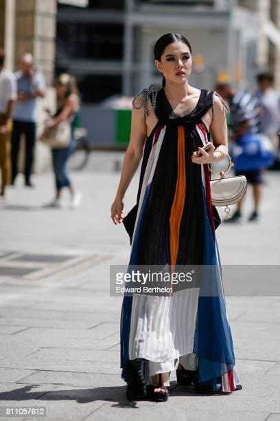 A guest wears a white semicircular bag a long ruffle multicolor stripe dress outside Alexis Mabille during Paris Fashion Week Haute Couture...