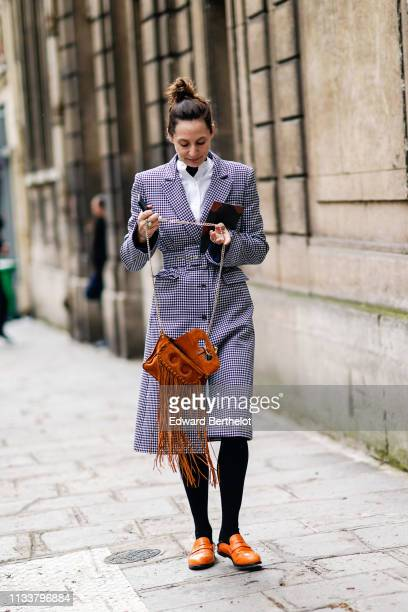 A guest wears a white shirt a black and white gingham coat a tannishyellow fringe bag black tights gold leather shoes outside Nobi Talai during Paris...
