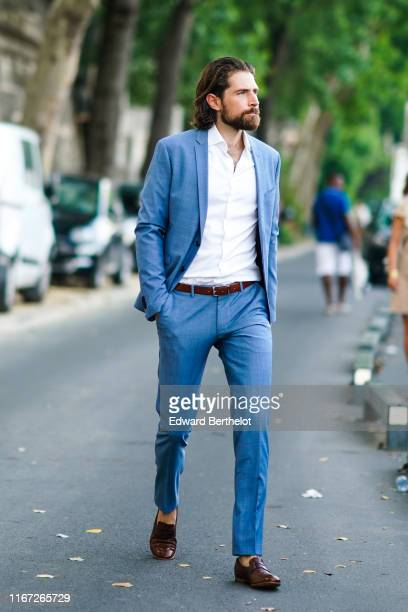 Guest wears a white shirt, a blue suit, a brown belt, brown moccasins, outside the Kerastase Party At Port Debilly, on June 26, 2019 in Paris, France.