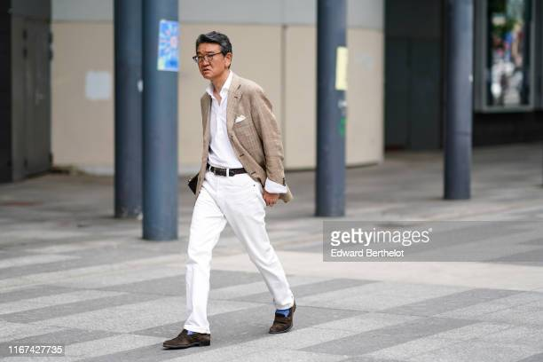 A guest wears a white shirt a brown alligator pattern belt white denim cuffed pants blue socks brown suede moccasins a light brown and creamcolor...