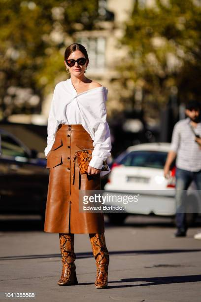 A guest wears a white shirt a brown leather skirt brown leather snake print boots outside Rochas during Paris Fashion Week Womenswear Spring/Summer...
