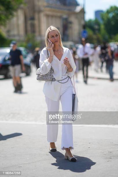 A guest wears a white shirt a Chanel belt a Chanel tweed bag ripped white pants Chanel slingback shoes outside Chanel during Paris Fashion Week Haute...