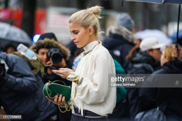 Guest wears a white shirt, a green crocodile pattern leather bag, a necklace, outside Chloe, during Paris Fashion Week - Womenswear Fall/Winter...