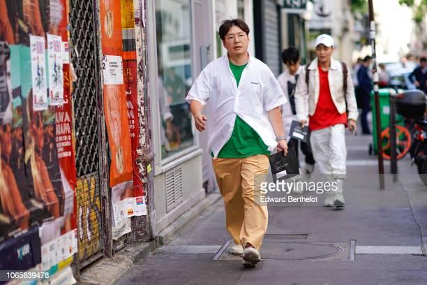 A guest wears a white shirt a green tshirt flare pants sneaker shoes outside Yohji Yamamoto during Paris Fashion Week Menswear SpringSummer 2019 on...