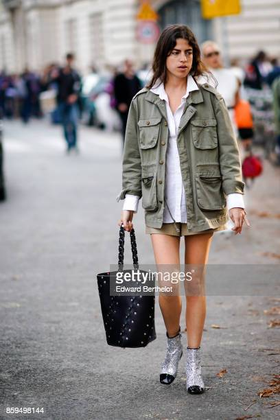 A guest wears a white shirt a khaki military jacket light khaki shorts a black bag silver lame and black boots outside the Rochas show during Paris...