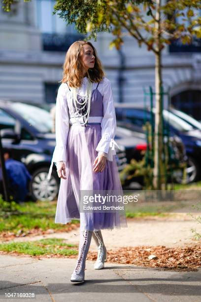 A guest wears a white shirt a purple mesh lace dress boots with shoelaces outside Akris during Paris Fashion Week Womenswear Spring/Summer 2019 on...