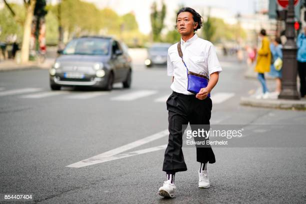 A guest wears a white shirt a Vuitton bag black cropped pants white sneakers outside Anrealage during Paris Fashion Week Womenswear Spring/Summer...