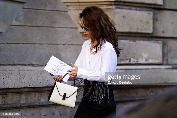 A guest wears a white shirt a white bag outside Valentino during Paris Fashion Week Haute Couture Fall/Winter 2019/2020 on July 03 2019 in Paris...
