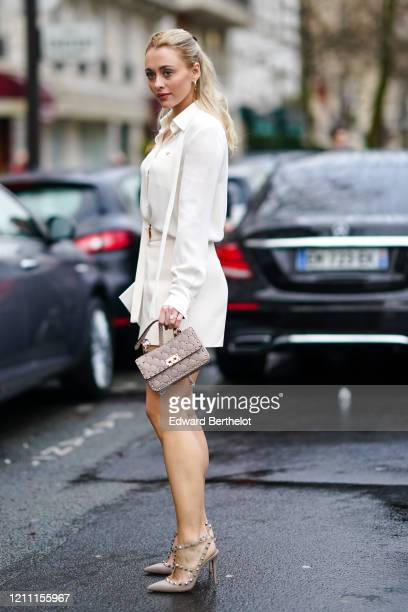 Guest wears a white shirt, a white skirt, a Valentino studded bag, pointy high heeled studded shoes, earrings, outside Valentino, during Paris...