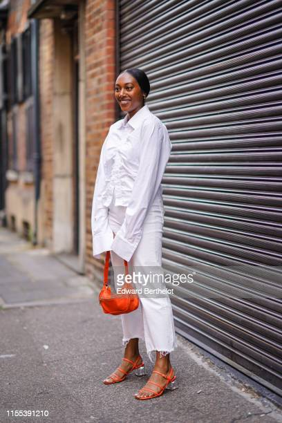 A guest wears a white shirt an orange bag white denim pants orange shoes with clear plastic heels during London Fashion Week Men's June 2019 on June...