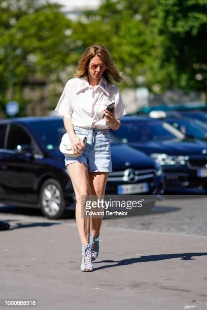 A guest wears a white shirt blue denim shorts a bag outside OffWhite during Paris Fashion Week Menswear SpringSummer 2019 on June 20 2018 in Paris...