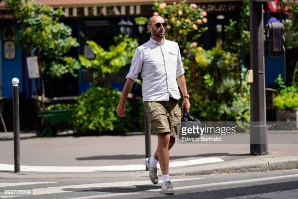 A guest wears a white shirt green khaki shorts white socks sneakers shoes outside Wooyoungmi during Paris Fashion Week Menswear SpringSummer 2019 on...