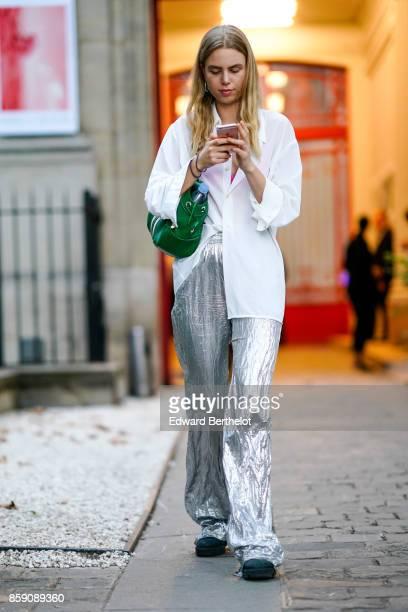 A guest wears a white shirt silver pants a green bag outside Kaviar Gauche during Paris Fashion Week Womenswear Spring/Summer 2018 on September 29...