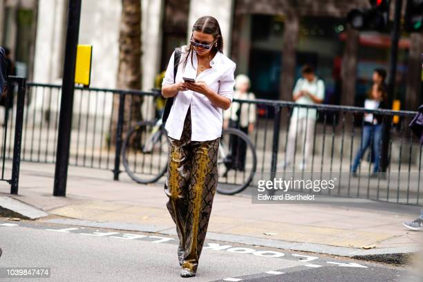 A guest wears a white shirt snake print leather flared pants during London Fashion Week September 2018 on September 18 2018 in London England