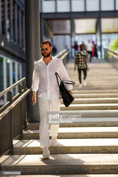 A guest wears a white shirt white pants outside Issey Miyake during Paris Fashion Week Menswear SpringSummer 2019 on June 21 2018 in Paris France