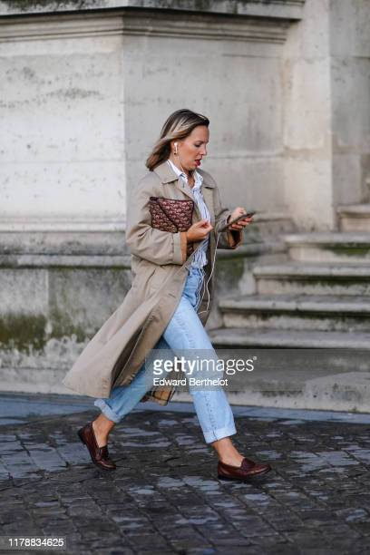Guest wears a white shirt with blue stripes, light blue denim rolled-up pants, a beige trench coat, a red Dior monogram clutch, brown moccasins,...