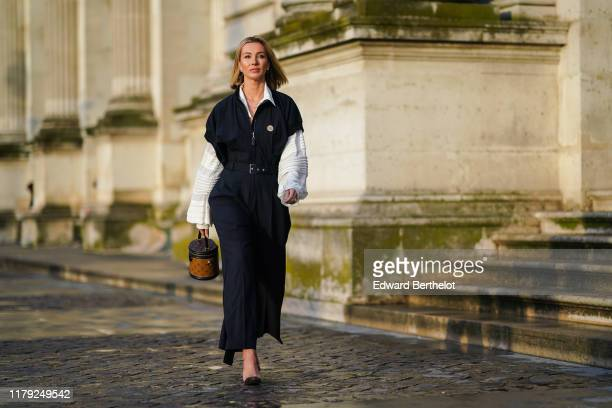 A guest wears a white shirt with flared and striped sleeves a dark jumpsuit a Vuitton brown bag shaped as a cylinder earrings outside Louis Vuitton...