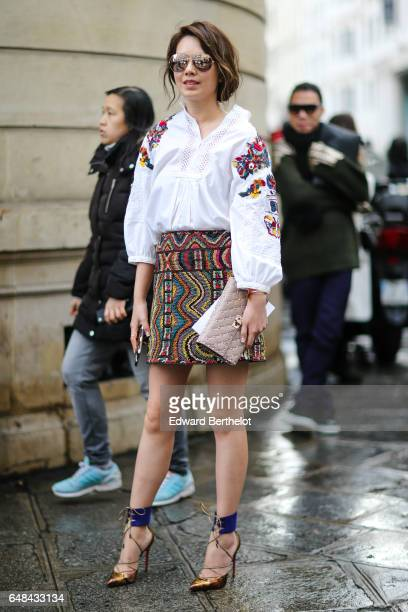 A guest wears a white shirt with flower print and a multicolor skirt outside the Valentino show during Paris Fashion Week Womenswear Fall/Winter...