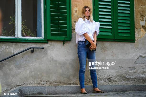 Guest wears a white shirt with oversized puffy short sleeves, blue denim jeans pants, red bracelets, a black leather clutch, silver rings, beige and...