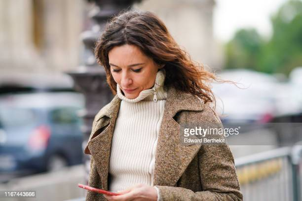 A guest wears a white sidezip turtleneck a light brown tweed jacket outside the Chanel Cruise Collection 2020 At Grand Palais on May 03 2019 in Paris...