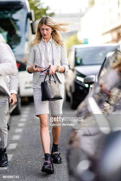 A guest wears a white striped blazer jacket a white shirt a tie shorts black shoes outside 1017 ALYX 9SM during Paris Fashion Week Menswear...