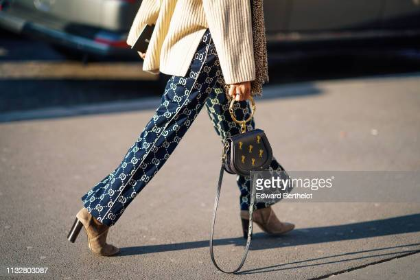 Guest wears a white sweater, a leopard print scarf, navy blue Gucci flare pants, a black Chloé bag, camel boots, outside Rochas, during Paris Fashion...