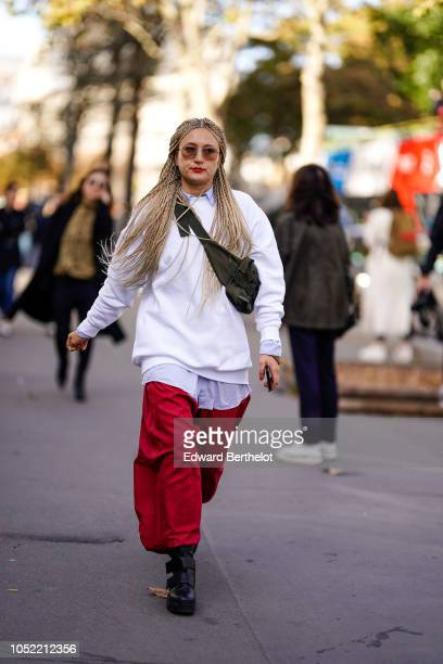 A guest wears a white sweater red pants a shoulder strapped fanny pack outside Haider Ackermann during Paris Fashion Week Womenswear Spring/Summer...
