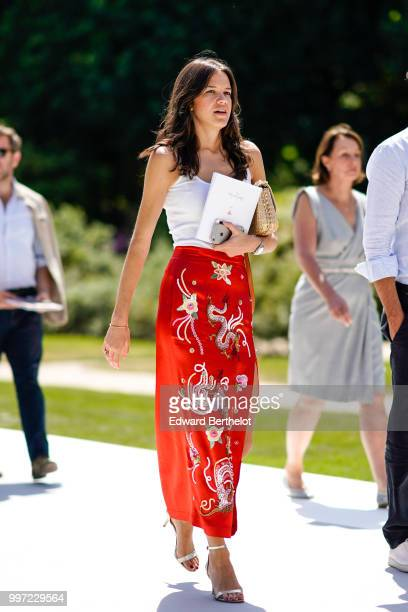 A guest wears a white tank top a red skirt with embroidered flowers outside Dior during Paris Fashion Week Haute Couture Fall Winter 2018/2019 on...