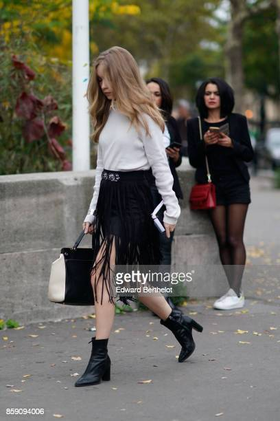 A guest wears a white top a bag black shoes a black skirt with fringes outside Andrew GN during Paris Fashion Week Womenswear Spring/Summer 2018 on...