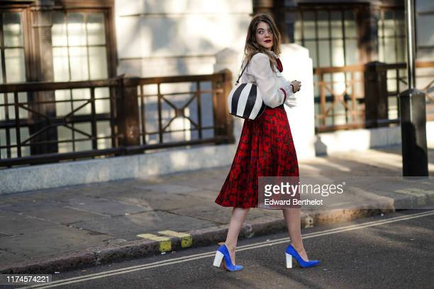 Guest wears a white top, a black and white striped bag, a red skirt with printed pattern, blue shoes with white heels, during London Fashion Week...