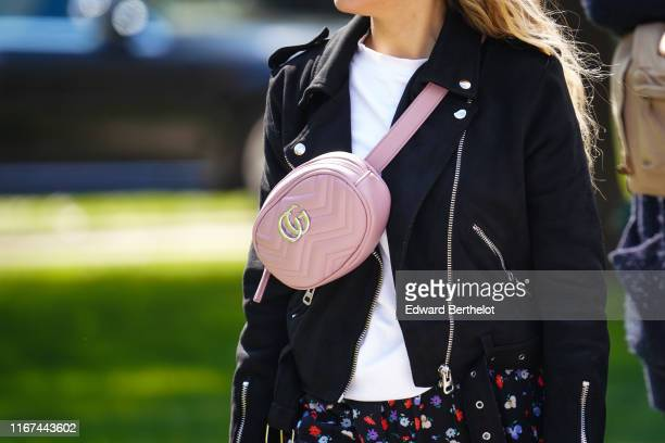 A guest wears a white top a black biker jacket a pink Gucci belt bag a floral print black skirt outside the Chanel Cruise Collection 2020 At Grand...