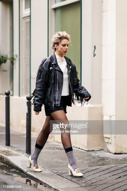 A guest wears a white top a black leather fringe black shorts cream color Gucci shoes outside APC during Paris Fashion Week Womenswear Fall/Winter...